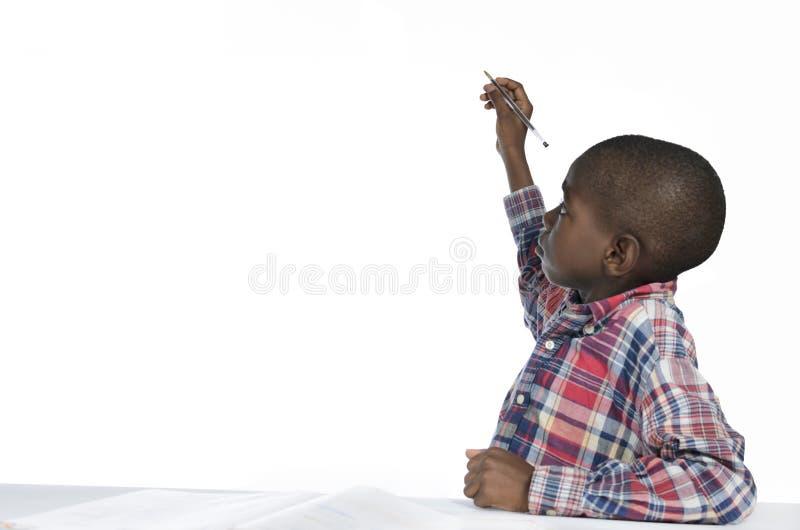 Африканское сочинительство мальчика с карандашем, космосом бесплатной копии стоковые изображения