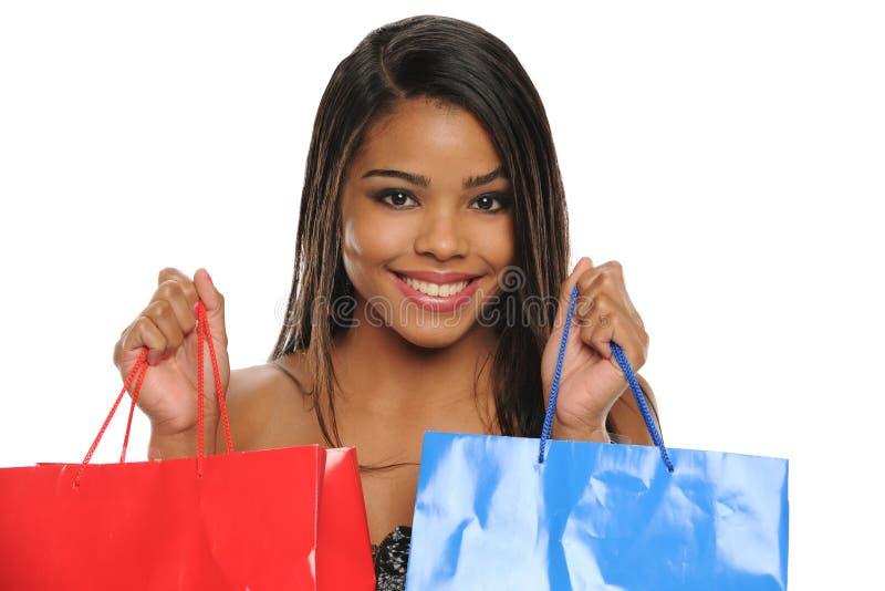 афроамериканец кладет детенышей в мешки женщины покупкы удерживания стоковые изображения rf