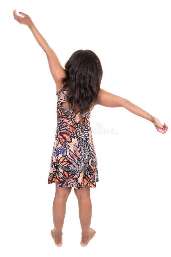 Афроамериканец молодой красивой женщины бразильский с вьющиеся волосы нося платье Африки стоя назад смотрящ прочь с оружиями ввер стоковые изображения rf