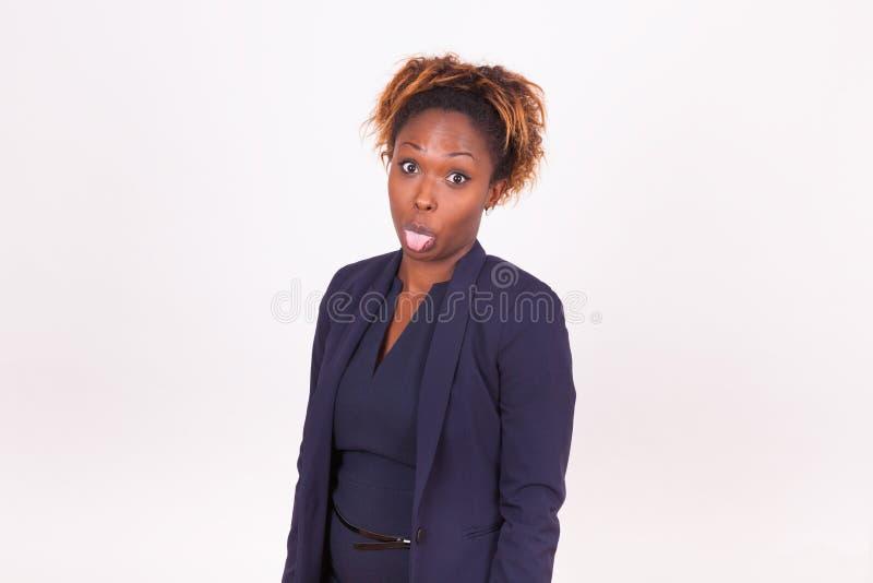 Афро-американская бизнес-леди вставляя язык вне стоковая фотография