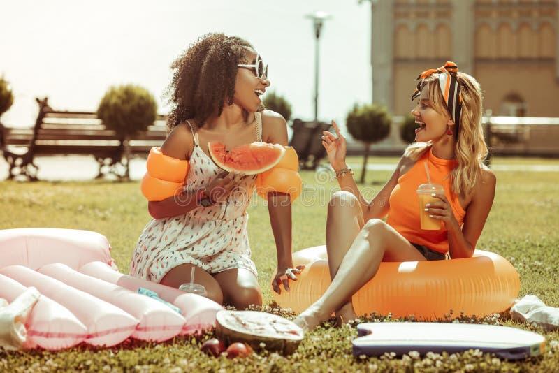 Афро-американская дама говоря с белокурым другом во время партии курицы стоковое изображение rf