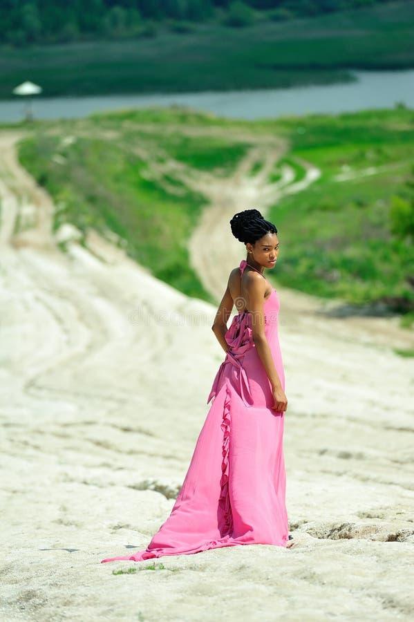 Афро-американская девушка с dreadlocks, в розовом платье, стоя с ей назад на холме на заднем плане стоковое фото