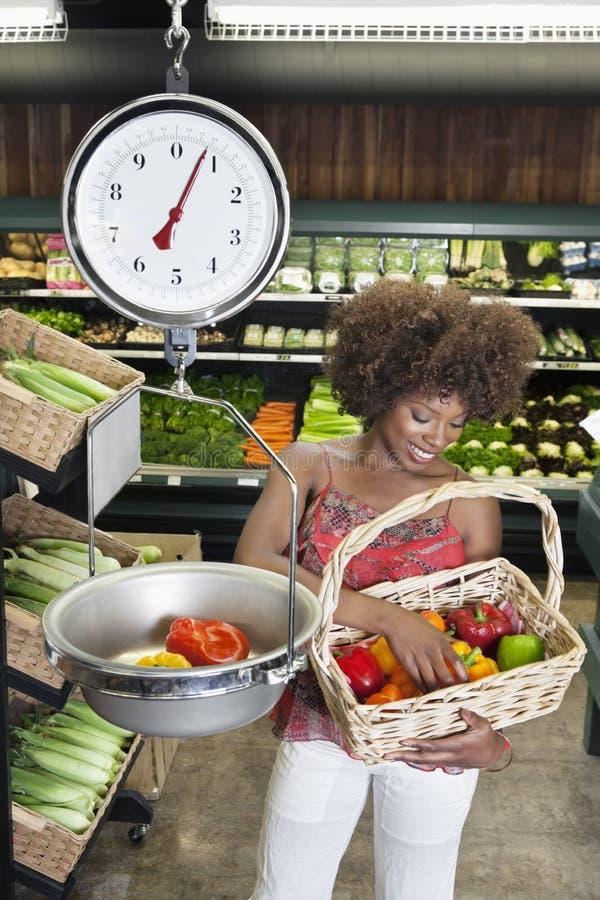 Афро-американская женщина веся болгарские перцы на масштабе на супермаркете стоковое фото