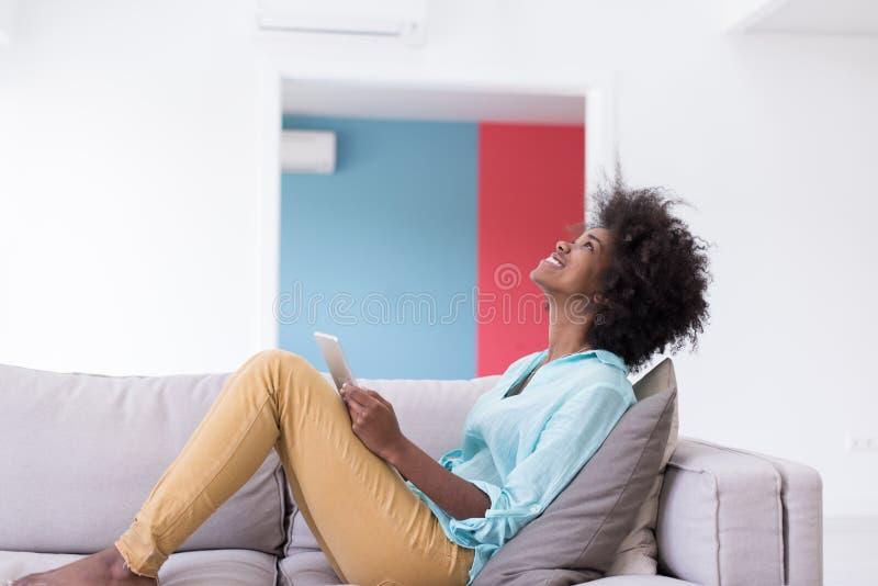 Афро-американская женщина дома используя цифровую таблетку стоковая фотография rf