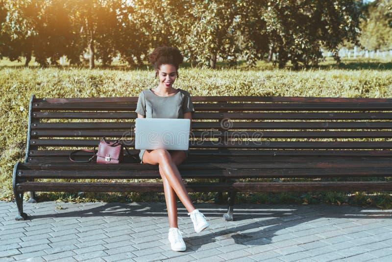 Афро-американская женщина на скамейке в парке с компьтер-книжкой стоковое фото rf