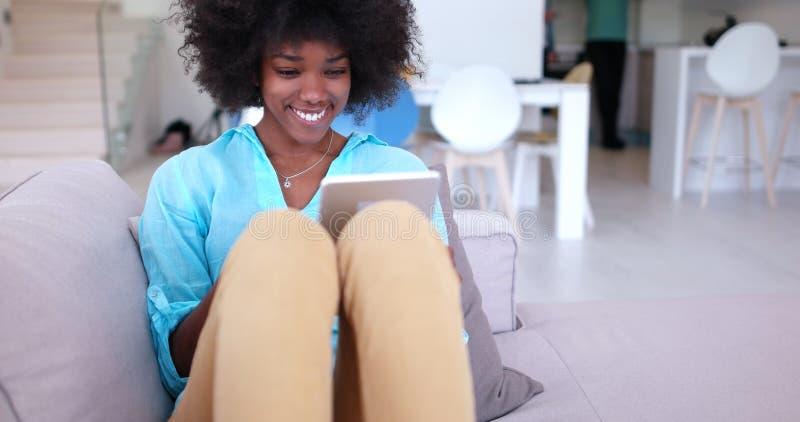 Афро-американская женщина дома используя цифровую таблетку стоковое фото