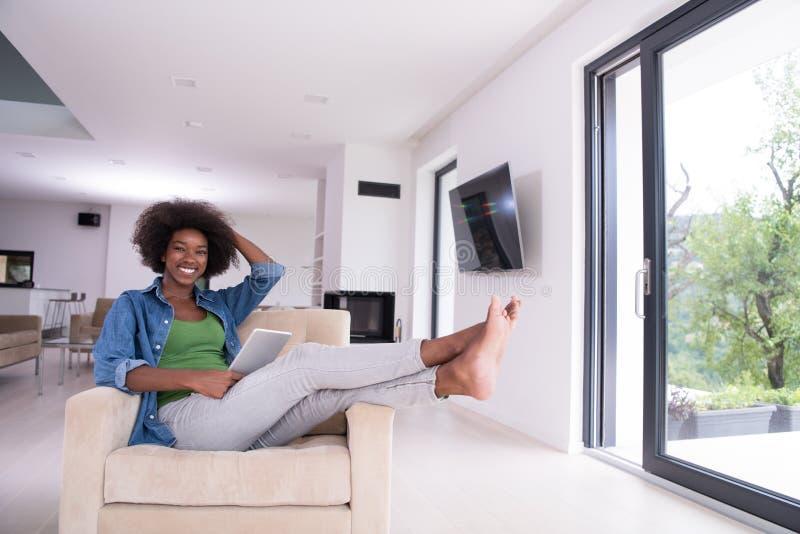 Афро-американская женщина дома с цифровой таблеткой стоковые изображения