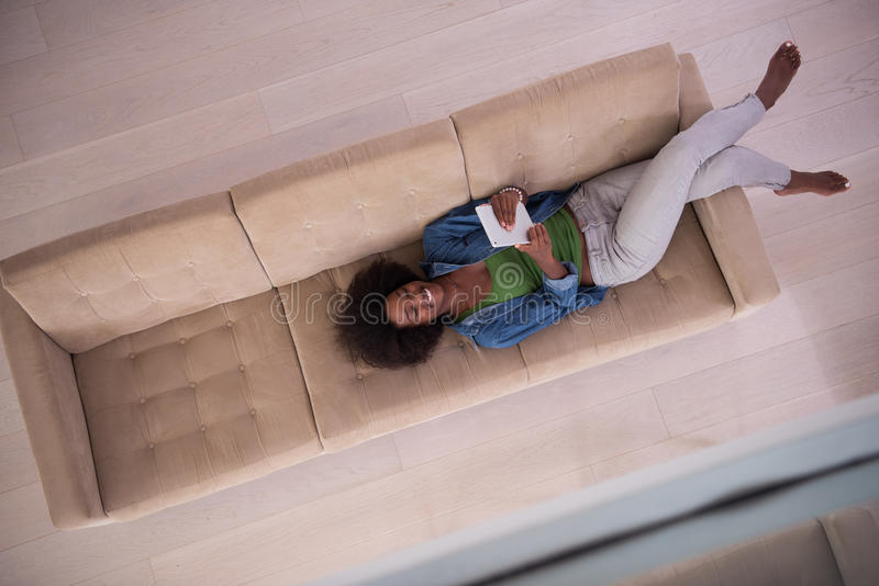 Афро-американская женщина дома с цифровым взгляд сверху таблетки стоковая фотография