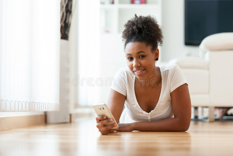 Афро-американская женщина посылая текстовое сообщение на мобильном телефоне стоковое фото