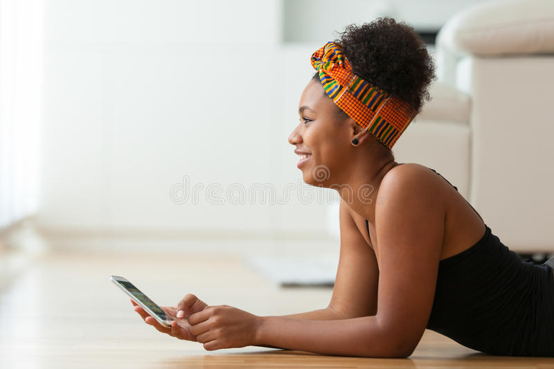 Афро-американская женщина посылая текстовое сообщение на мобильном телефоне стоковые изображения rf