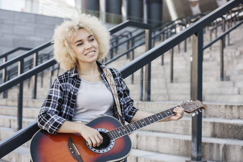 Афро-американская жизнерадостная девушка играя акустическую гитару стоковая фотография