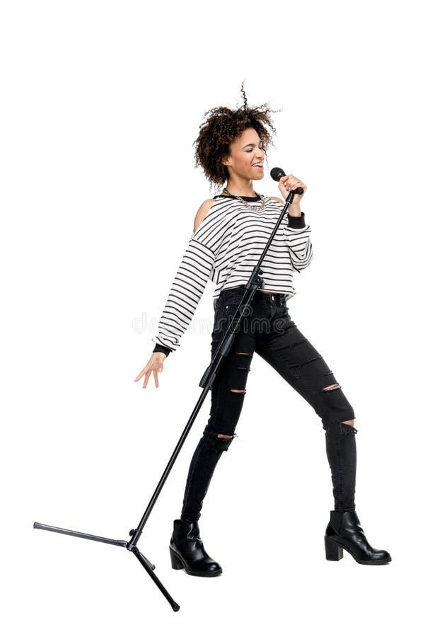 Афро-американская молодая женщина поя при микрофон изолированный на белизне стоковое изображение rf