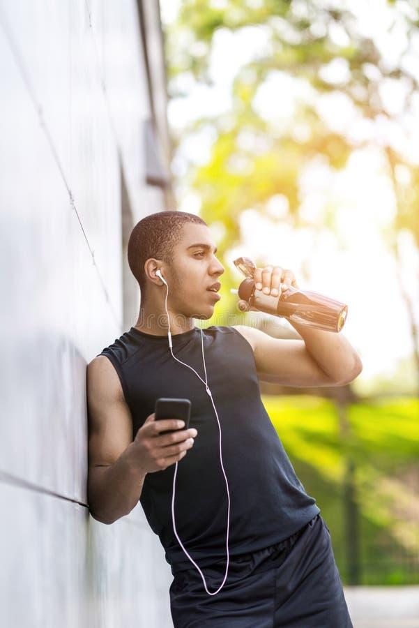 Афро-американская питьевая вода спортсмена стоковые изображения rf