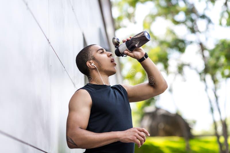 Афро-американская питьевая вода спортсмена стоковое фото rf