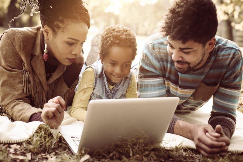Афро-американская семья в парке и использовать компьтер-книжке совместно стоковое изображение