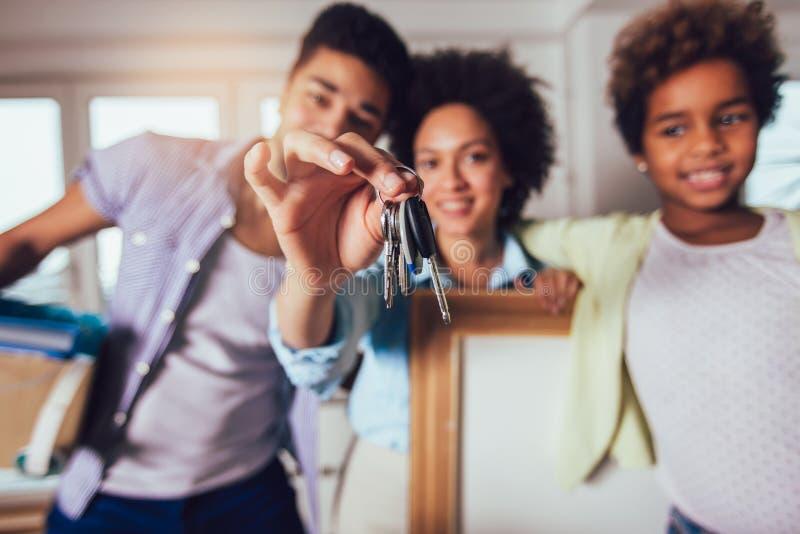 Афро-американская семья двигает в новую квартиру, они держит ключи от квартиры в их руках и смотрит стоковая фотография rf