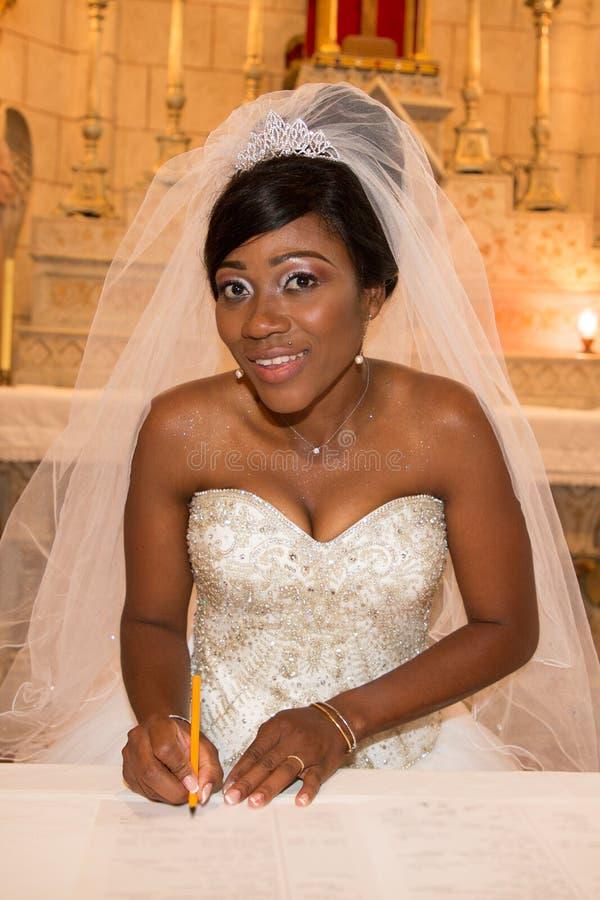 Афро-американская черная невеста которая подписывает регистр во время свадебной церемонии на церков стоковая фотография