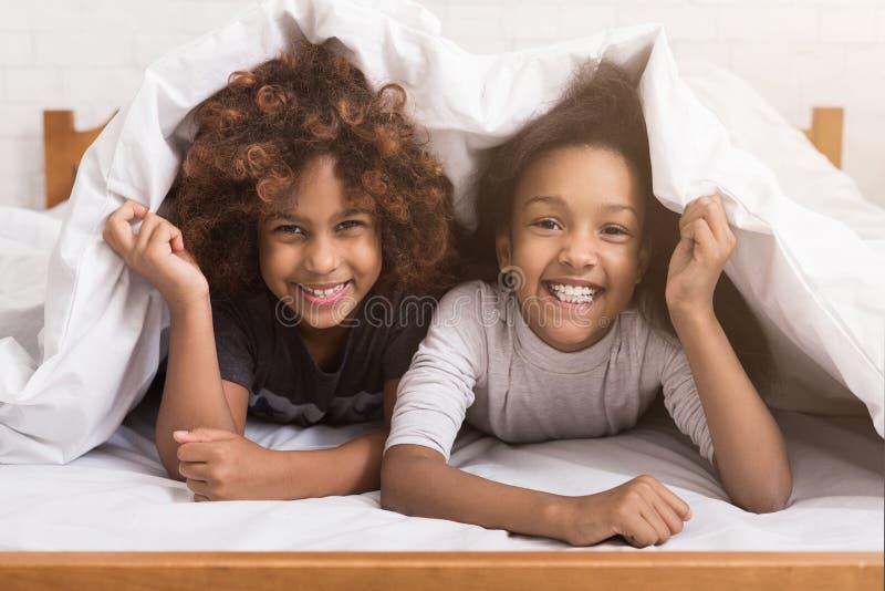 Афро-американские девушки ребенка лежа под одеялом на кровати стоковые фотографии rf