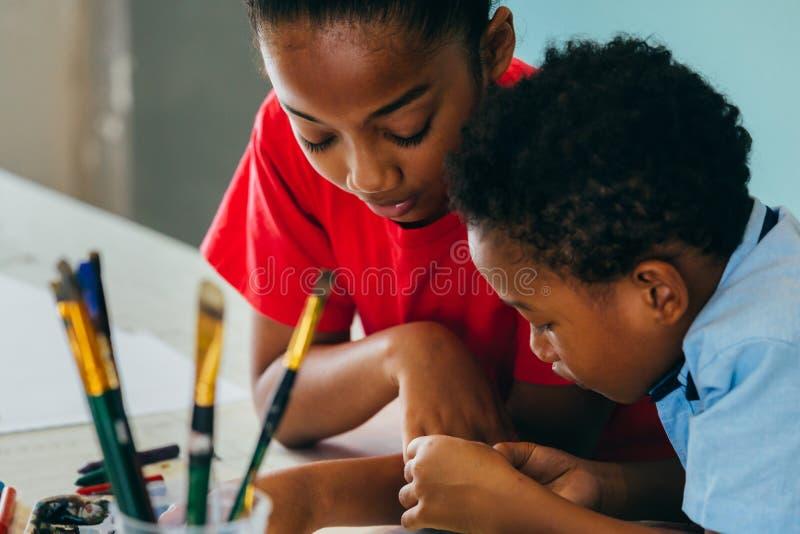 Афро-американские дети рисуя и крася стоковое фото
