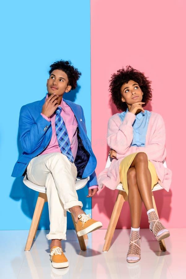 Афро-американские задумчивые пары сидя на стульях против пинка и сини стоковая фотография