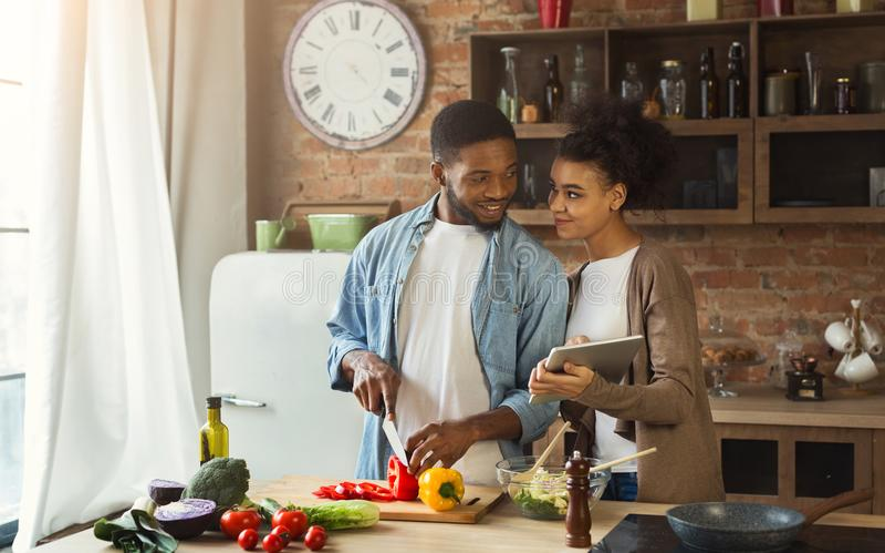 Афро-американские пары ища для рецепта используя цифровую таблетку стоковое фото rf