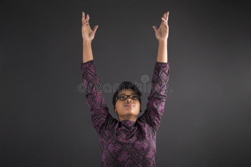 Афро-американские учитель или студент женщины достигая для неба стоковое фото