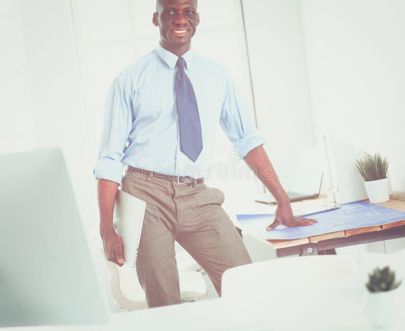 Афро-американский архитектор работая с компьютером и светокопиями в офисе стоковое фото rf