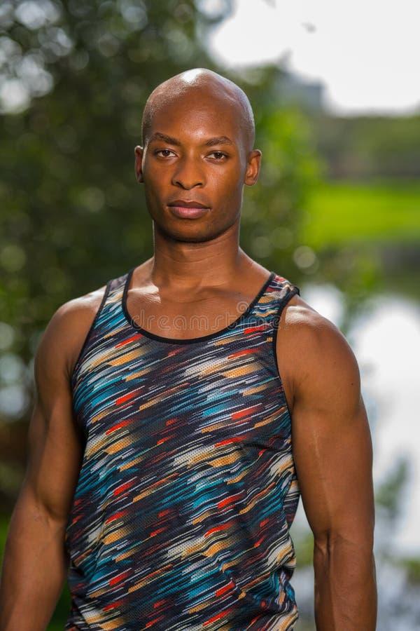 Афро-американский атлетический человек представляя outdoors в парке стоковые фото