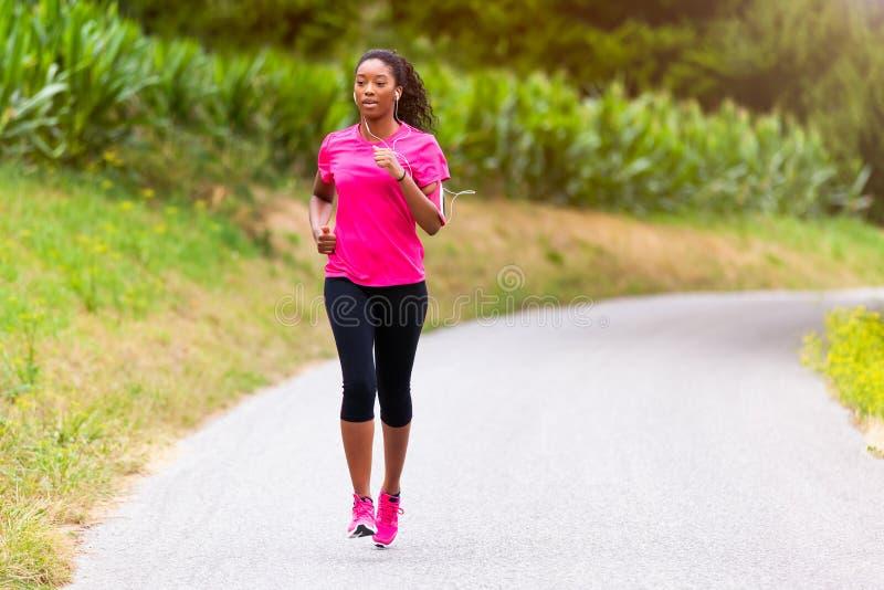 Афро-американский бегун женщины jogging outdoors - фитнес, peopl стоковые фото