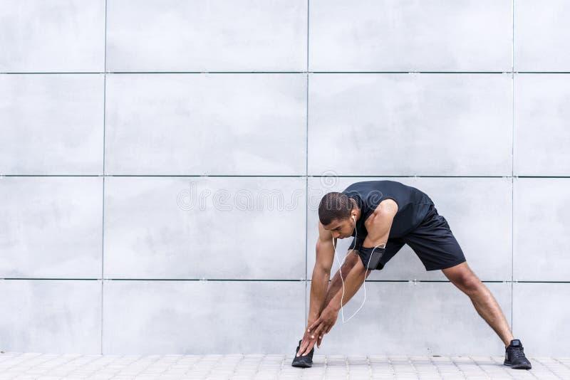 Афро-американский бегун протягивая на улице стоковое фото rf