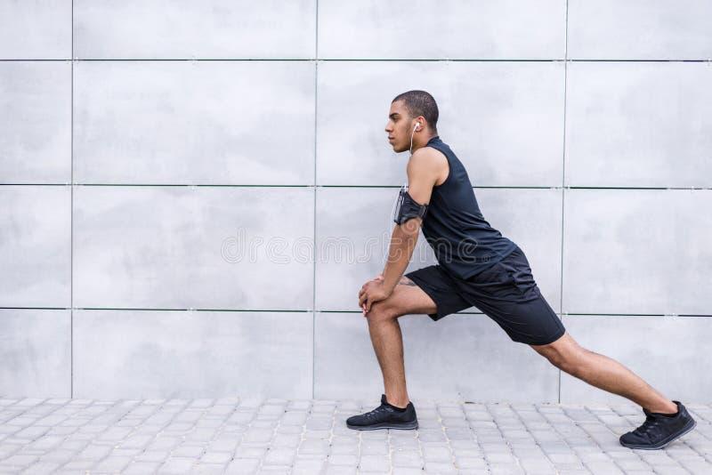 Афро-американский бегун протягивая на улице стоковая фотография