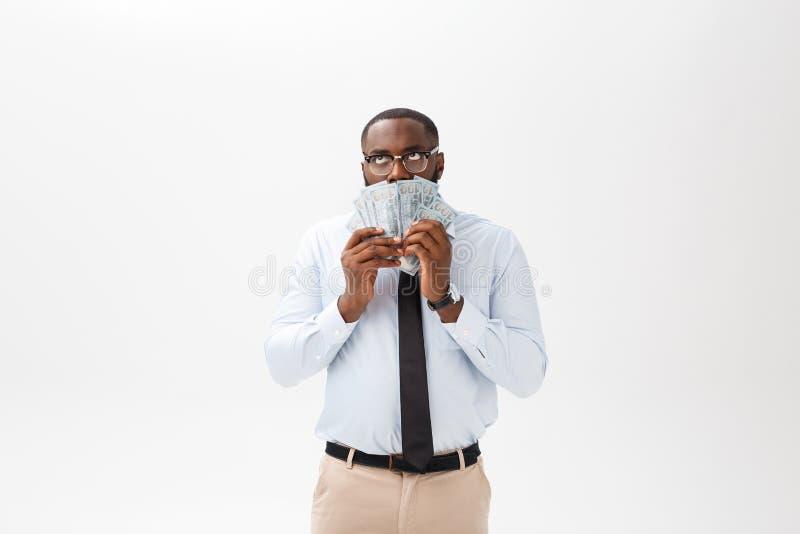 Афро-американский бизнесмен держа наличные деньги и серьезную смотря камеру Крытый, изолированный на серой предпосылке стоковые фотографии rf