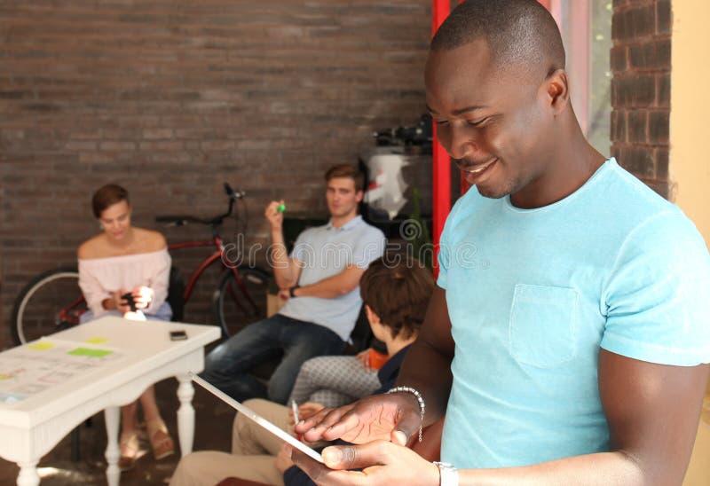 Афро-американский бизнесмен использует цифровую таблетку и усмехается пока сидящ в его офисе стоковое изображение rf