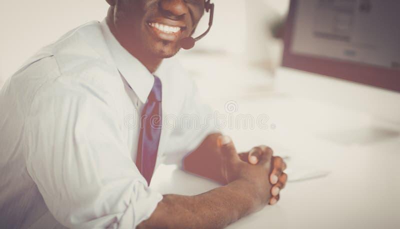 Афро-американский бизнесмен на шлемофоне работая на его компьтер-книжке стоковое фото rf