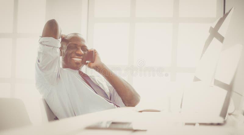 Афро-американский бизнесмен на шлемофоне работая на его компьтер-книжке стоковая фотография rf