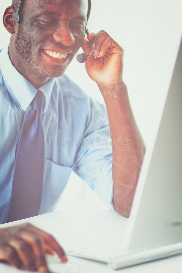 Афро-американский бизнесмен на шлемофоне работая на его компьтер-книжке стоковое изображение rf