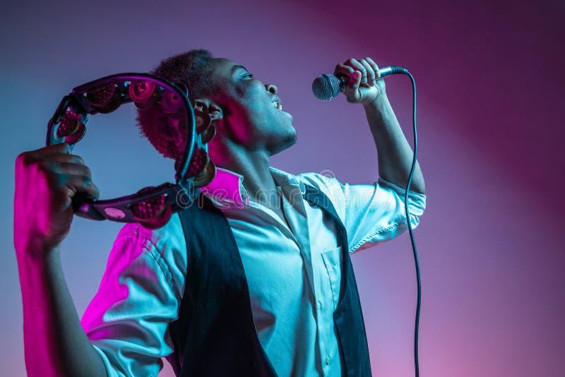 Афро-американский красивый джазовый музыкант играя тамбурин и поя стоковые фото
