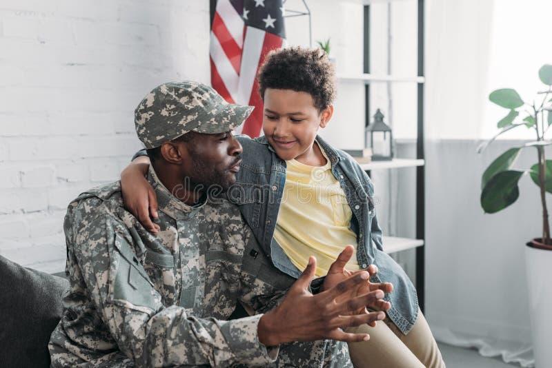 Афро-американский мальчик обнимая и слушая к его отцу стоковые изображения