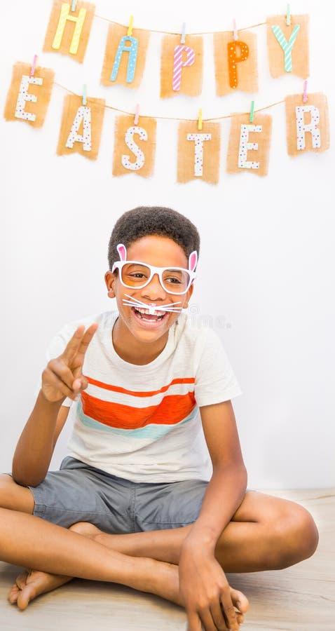 Афро-американский мальчик с смеяться над стекел зайчика Острословие предпосылки стоковое изображение rf