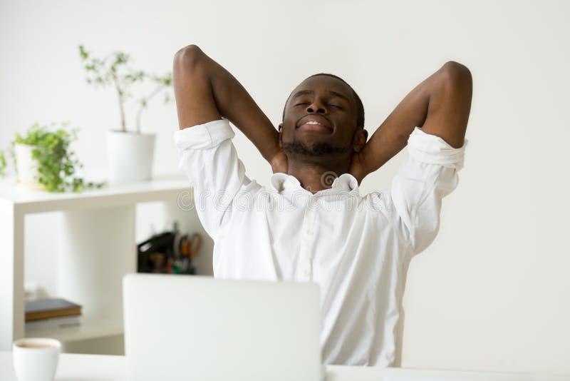 Афро-американский молодой бизнесмен ослабляя на работе дышая fr стоковая фотография rf