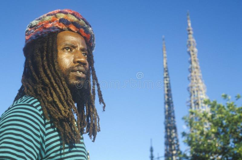 Афро-американский мужчина представляет с башнями ватт, двадцатой годовщиной 1965 бунтов, Лос-Анджелесом, Калифорнией стоковое фото rf