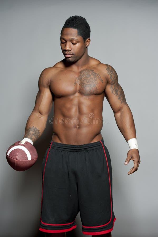 Афро-американский мужчина с футболом стоковое изображение