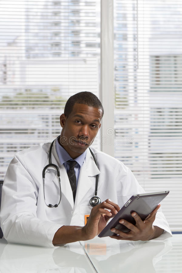 Афро-американский доктор используя электронную таблетку, вертикальную стоковое изображение