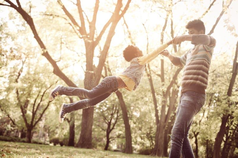 Афро-американский отец держа руки дочери и вращает внутри стоковое изображение rf