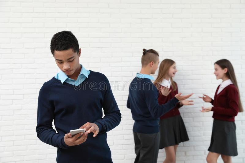 Афро-американский подросток предпочитая мобильный телефон к одноклассникам Концепция наркомании и одиночества интернета стоковое изображение