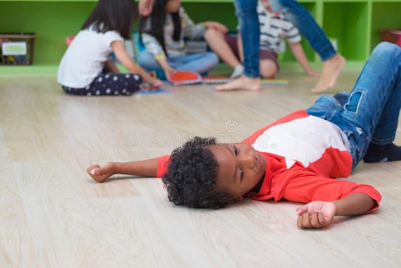 Афро-американский ребенк с эмоцией одиночества отдельный от группы стоковое фото rf