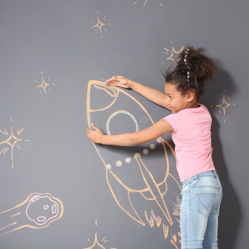 Афро-американский ребенок играя с чертежом ракеты мела на сером цвете стоковая фотография rf
