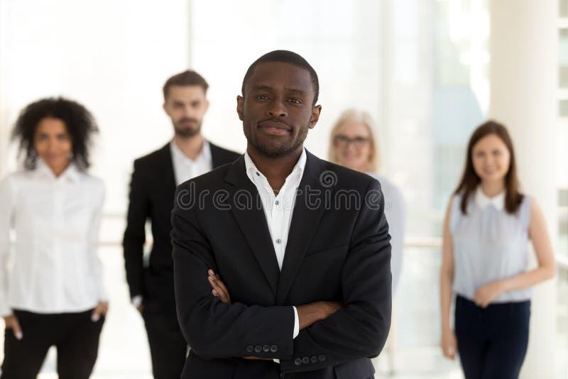 Афро-американский руководитель, босс с работниками объединяется в команду взгляд на камере стоковые изображения rf