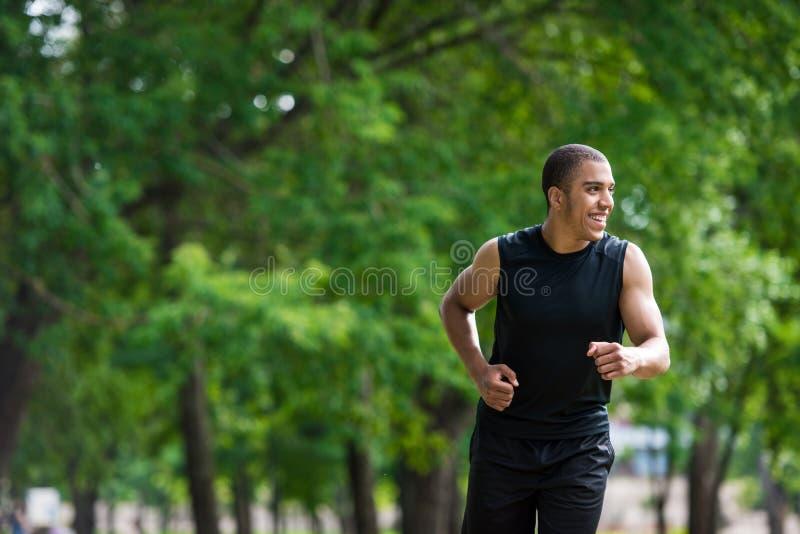 Афро-американский спортсмен бежать в парке стоковое изображение rf