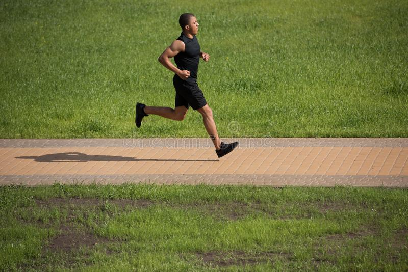 Афро-американский спортсмен бежать в парке стоковая фотография rf